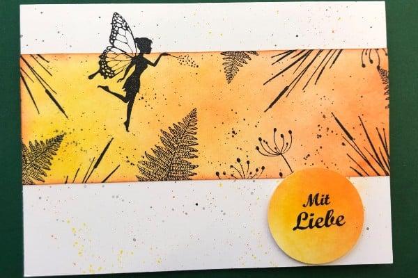 Erstellte Karte mit Motivstempeln einer fliegenden Fee über eine Blumenwiese